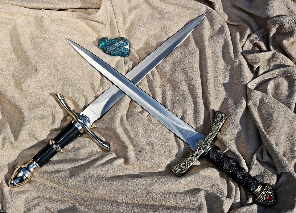 два скрещенных клинка и камень лежат на смятой ткани